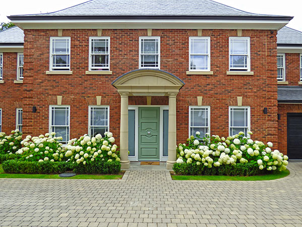 Large regency style house with hydrangeas players planed in front to complement and soften the visual approach